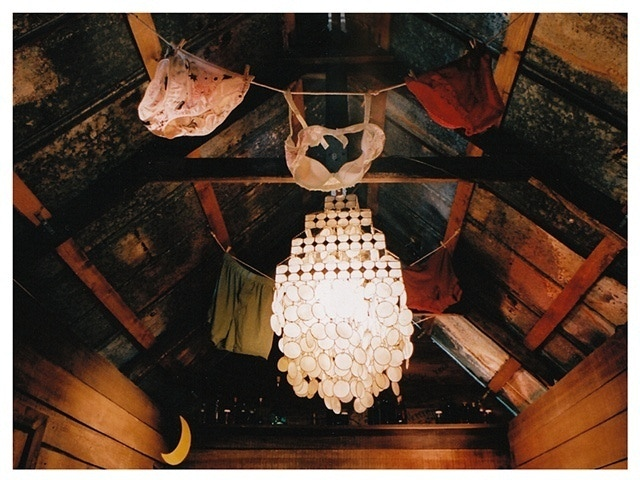 The ceiling of The Love Shack is covered with lines of lingerie and a vintage abalone chandelier.