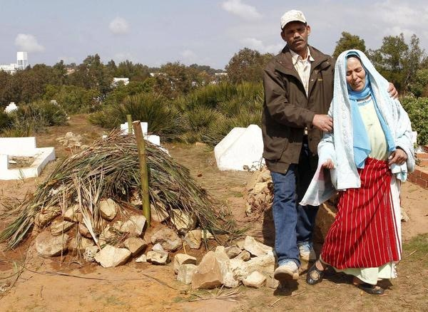 Amina's parents mourning near her grave in Larache, Morocco