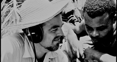 Alan Lomax and Raphael Hurtault listening to playback La Plaine, Dominica      Antoinette Marchand/Association for Cultural Equity