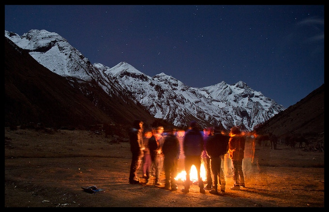 The team huddles around a fire on our first Trek