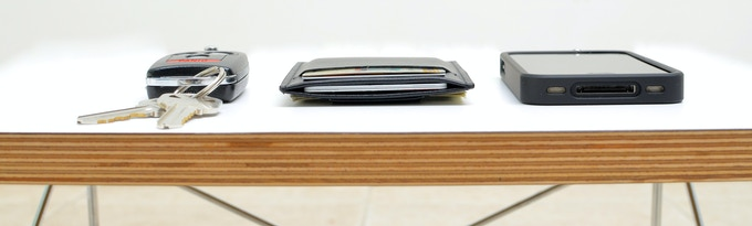 Thickness comparison: Key fob (left), Minimalist™ (center), iPhone 4 with case (right)
