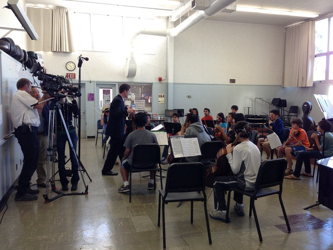 Cameraman Rob Englehardt and Director Ty Kim discuss a camera angle as PACO Guest Conductor Scott Krijnen inspires young musicians.