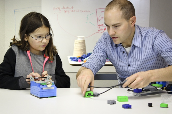 ATOMS University member works with Eric Budd, founding team member, to build a LEGO garage with a door that opens - using ATOMS.