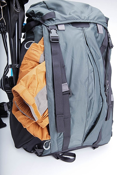 Side zip outer jacket pocket holds layers of clothes including a down jacket. It can accommodate smaller laptops with a user provided protective cover. Pack is shown with optional top pocket which further expands capacity (Included in Pledge #3).