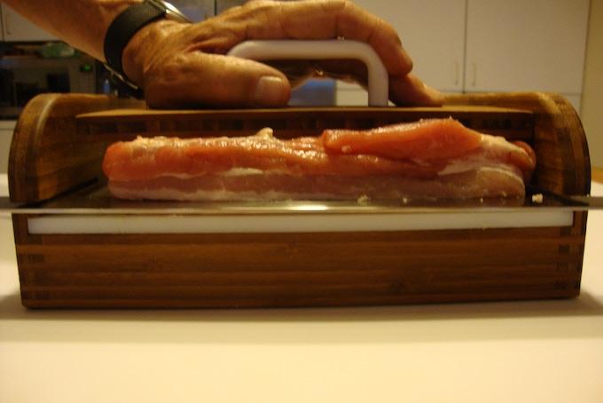 Slicing the rind off a slab of pork belly
