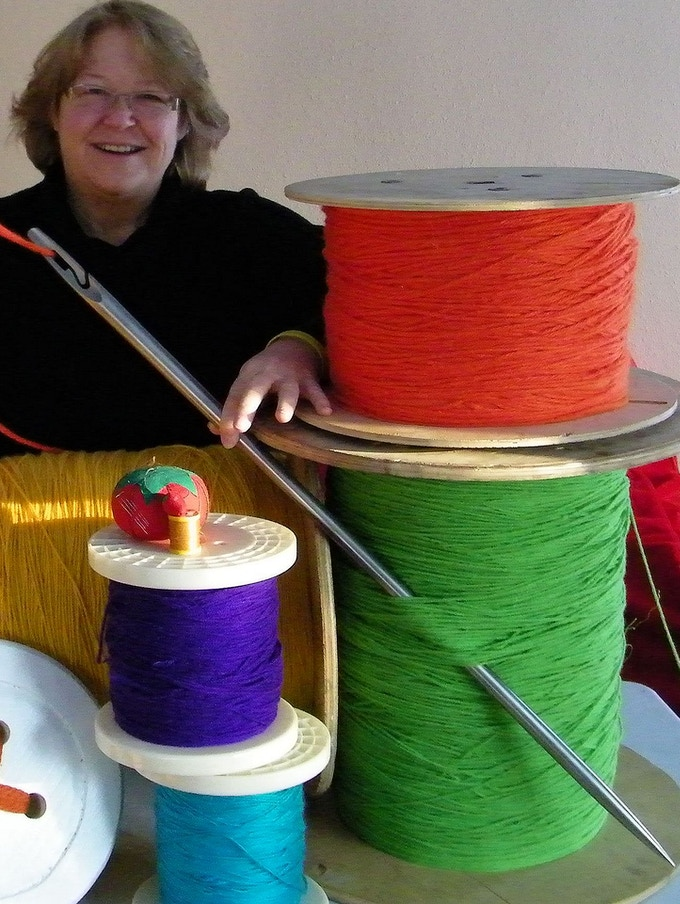Pam Turner uses a giant needle to demonstrate at shows