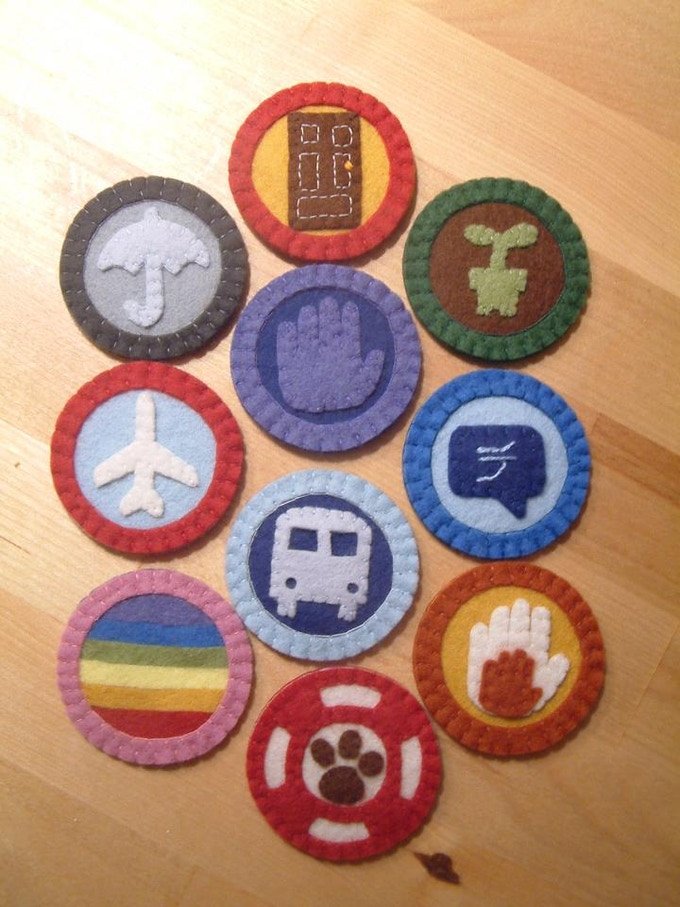 The 2013 series of merit badges represent (from bottom left upward)- coming out, traveling abroad, having a savings account, buying a home, planting a garden, learning a foreign language, working with children, adopting a rescue pet, taking public transit