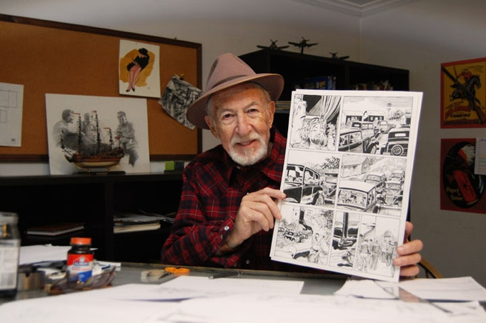 Gerald Forton holding a page of his original artwork from FREAKESTATE