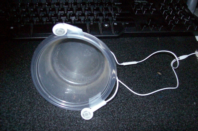 The Yuni, Mark I: iPhone earbuds taped to a plastic container.