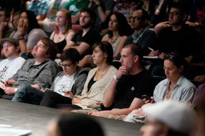 Attendees listening intently to their peers giving talks