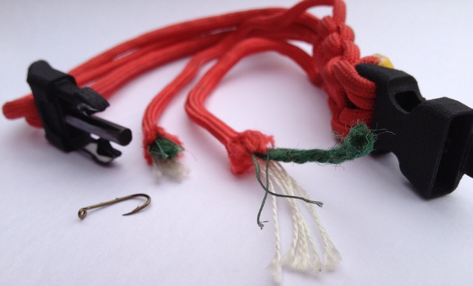 Survival cord with integrated fire starting tinder and braided fishing line