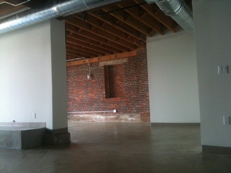 A view of our space - brick walls, exposed wood joists, concrete floor...