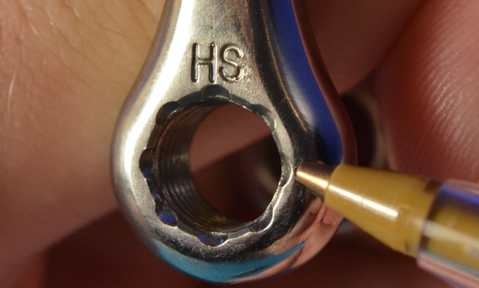 The notches on the shackle body. The HS designates that it is High Strength titanium.