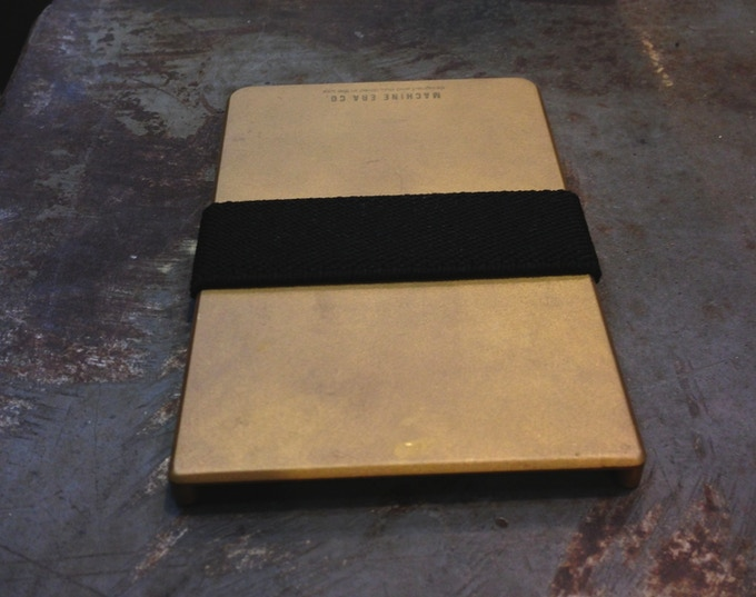 A broken in brass wallet with an aged patina.