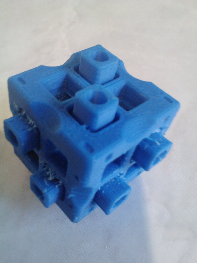 A prototype of the final design made on a home 3D printer.  Added moats around and holes inside of the pegs to enhance mechanical compression.  Also added tunnels through the block to enhance moldability.