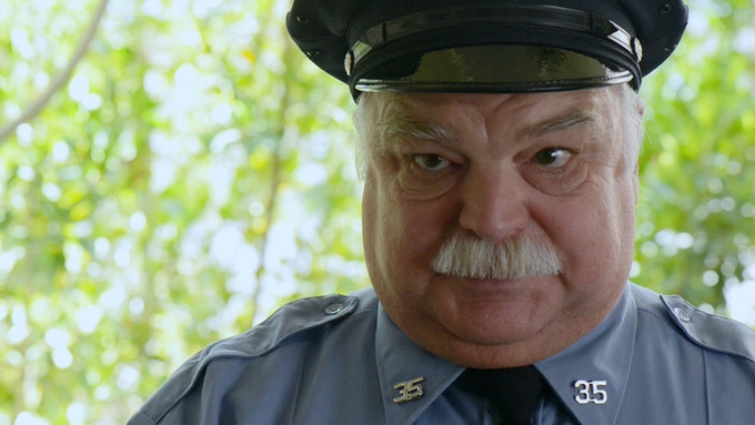 "Richard Riehle as ""Officer Braggs"""