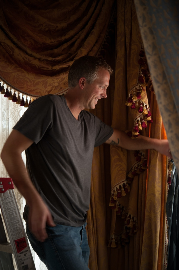 Nate Brunel, production designer, bulds out curtains, transforming a contemporary room into a parlor circa 1910