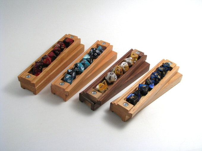 (Left to right:) Cherry with Red/Purple dice set, Douglas Fir with Shell dice set, Walnut with Gold/White dice set, Maple with blue/black dice set.