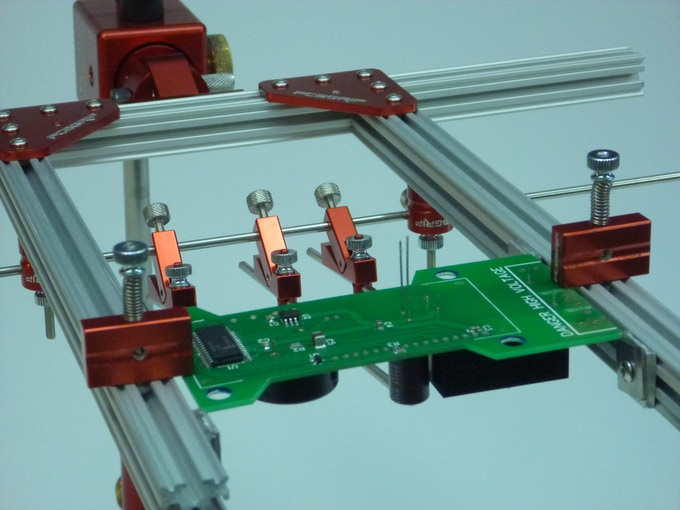 PCBGRIP holding PCB and through hole components for soldering.