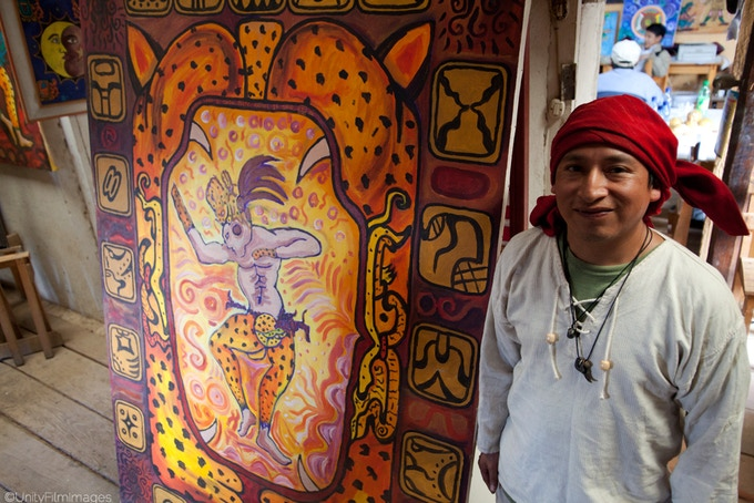 Artist Mario in front of his painting of the grand jaguar and Maya nawales