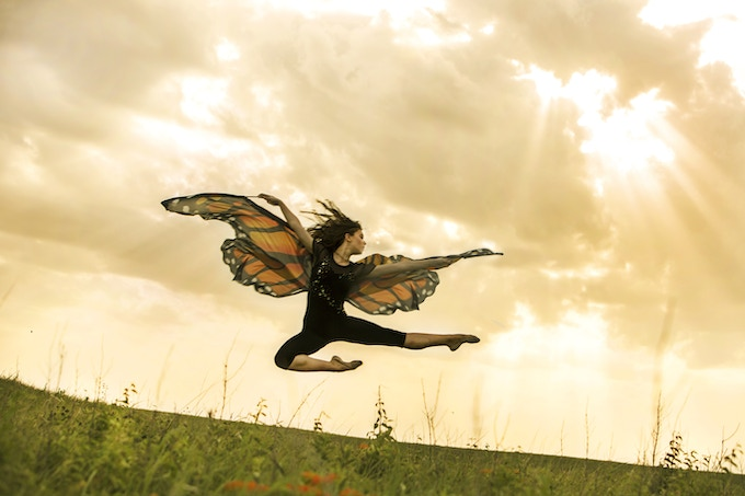 """""""In Flight,"""" Vetter-Drusch jumps over an orange variety of milkweed and other prairie flowers that support monarchs and other pollinators. Photo by Jaime Schirmer for Moving for Monarchs"""