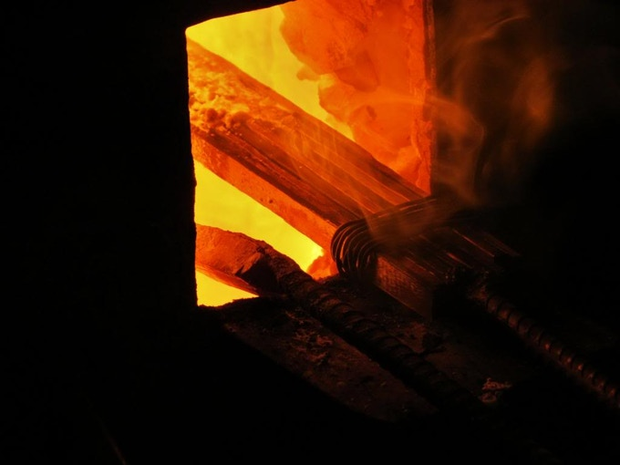 The billet of raw steel placed in the forge.