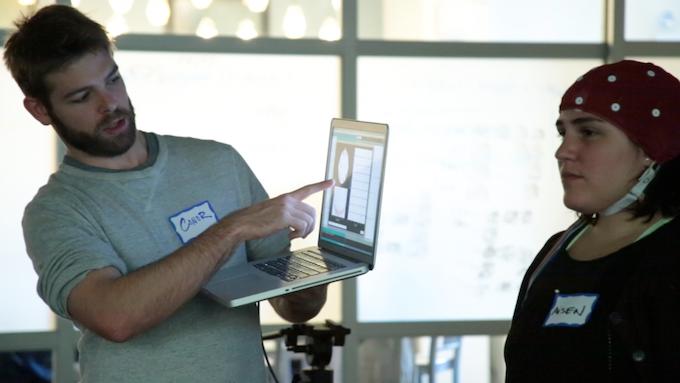 Conor explaining Aisen's brainwaves through the OpenBCI Brainwave Visualizer at a hackathon