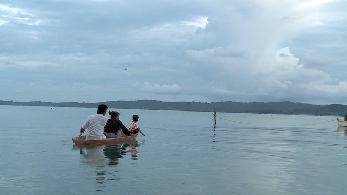 Han, Telurina, and their two youngest heading back to their boathouse for the night, during the height of the Lahad Datu incursion whilst the skies are patrolled by a military helicopter.