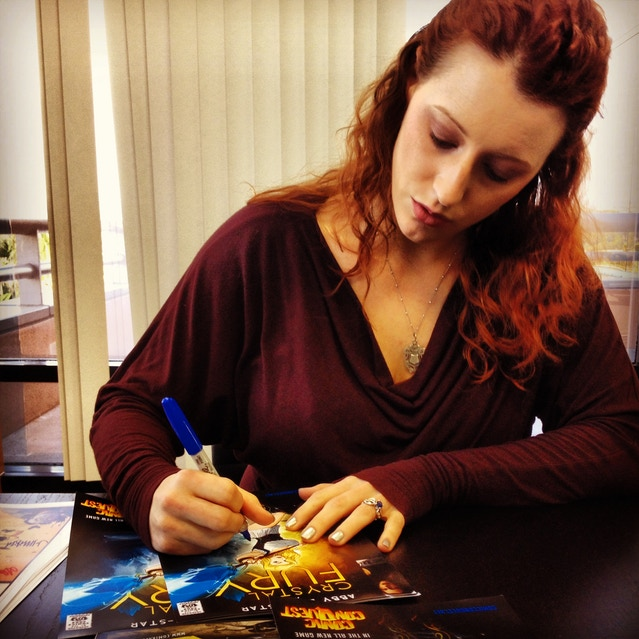 Abby autographing some swag for future giveaways.