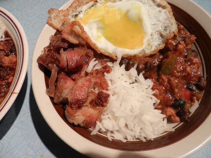 Cuban Black Beans with Chicharrone over rice topped with a fried eggs - one of my all time favorites.