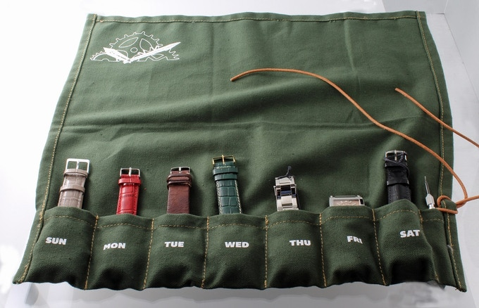 Green watch roll containing seven watches and a pin pusher for your reference.