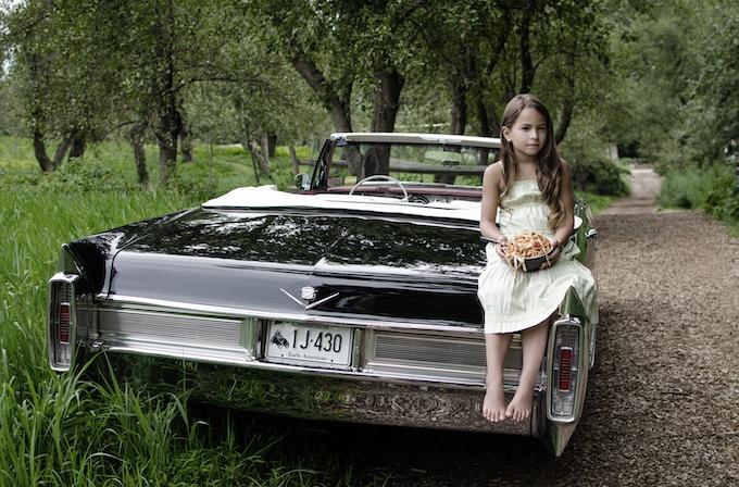 Allegra sitting on the back of Bobby V's car
