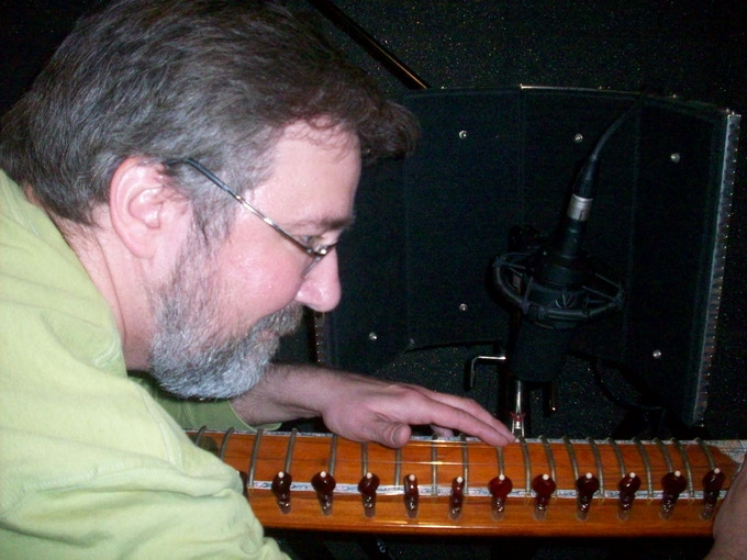 Tuning up the multi-stringed esraj for a recording session
