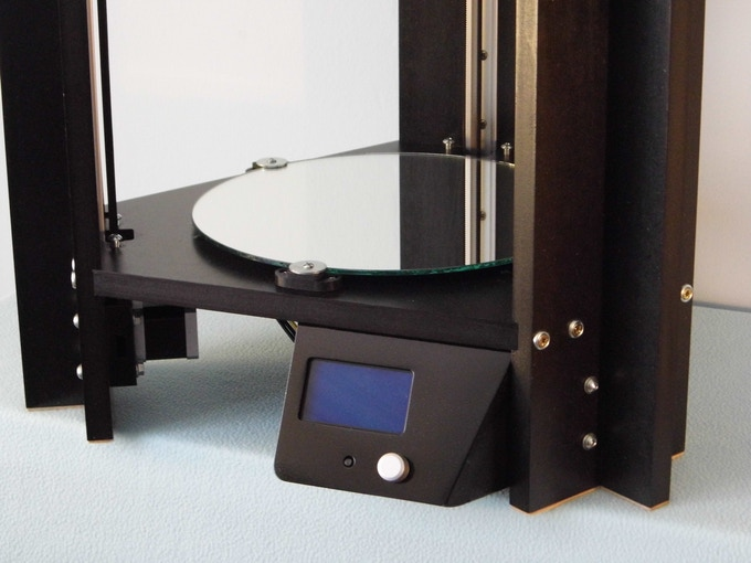 Round mirror glass forms the bed for our printer. Once covered with kapton tape, the heated pad underneath will enable good adhesion for printing parts in PLA and ABS.