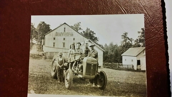 The day the tractor arrived! Grandma's sister is in the seat, with my aunt Janie, uncle Alfred (her twin) on the left and Grandpa on the right. The same cousin in Jim's photo below is on the hood.