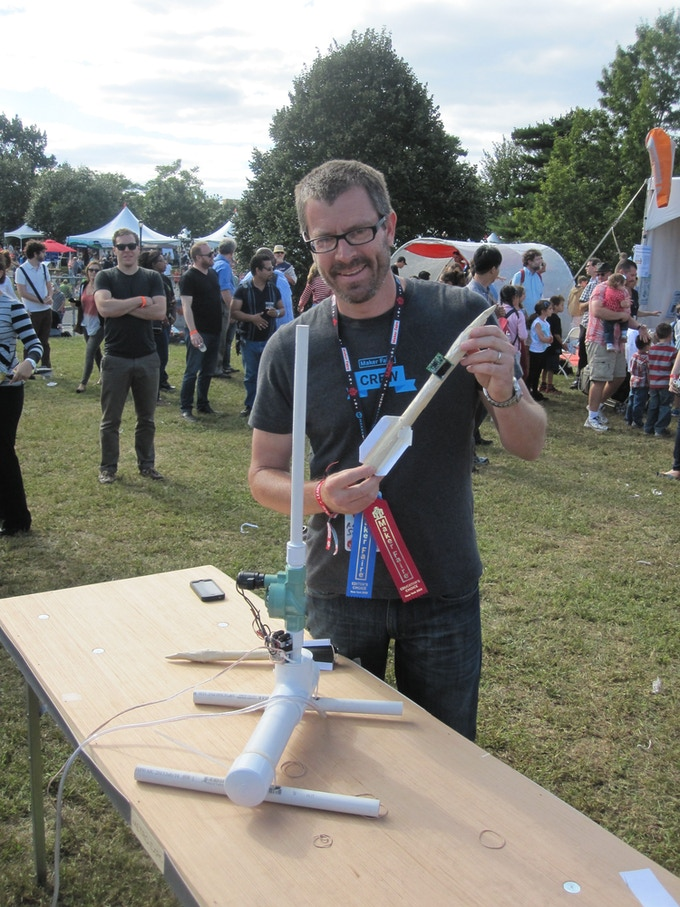 Rick at NY Maker Faire, test launching a functional prototype KickSat on a paper rocket, CAR v1.0 in foreground.  Thanks Zac!