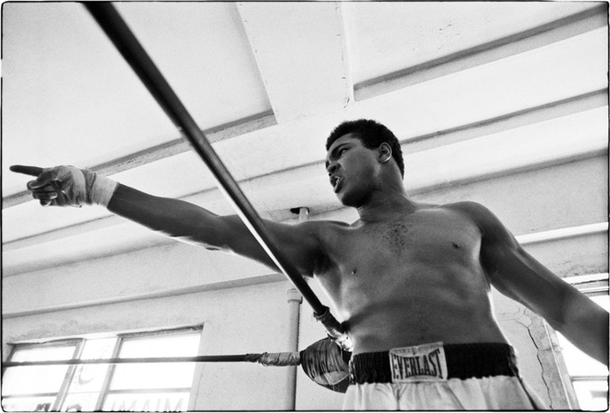 < D > Ali during a workout replying to sportswriters questions
