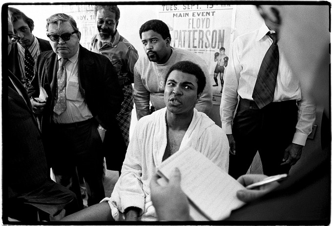 Muhammad Ali talking to the press after a workout