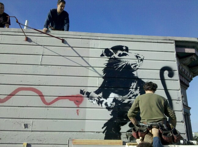 Workers begin work on recovering Banksy before it is painted over.
