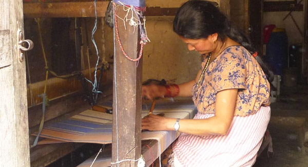 Weavers work from home on hand operated looms
