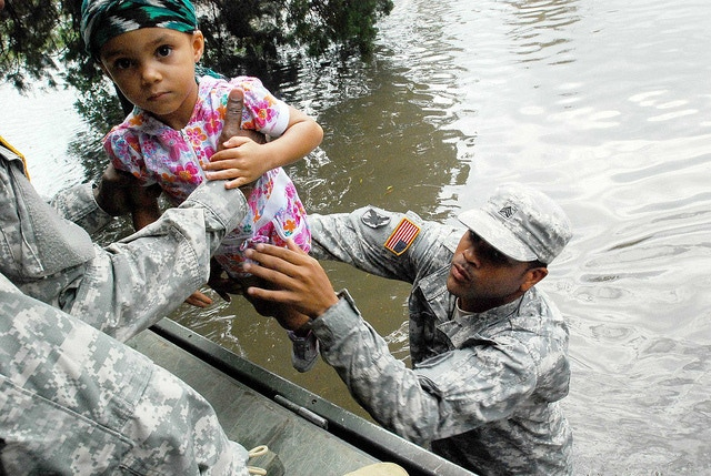Sgt. Lee Savoy, a soldier with the 256th Brigade Special Troops Battalion, Lousiana National Guard, evacuating a child in the wake of 2012's Hurricane Isaac. Photo by U.S. Army