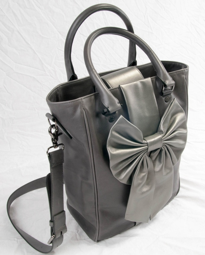 Sabine...the little sister to Samantha, also made out of cowhide w/ lambskin bow.  With at total of ten pockets, this bag is not only a fashionable choice but a functional one at that!!