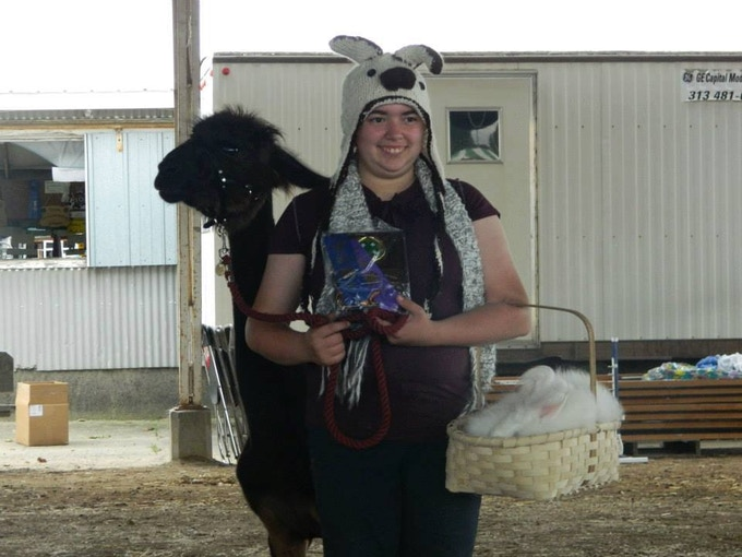Best in show lead with fiber. Wearing a handknit llama hat, a hanknit scarf, and a handknit backpack. Leading a llama and carying a bunny in a handmade basket.