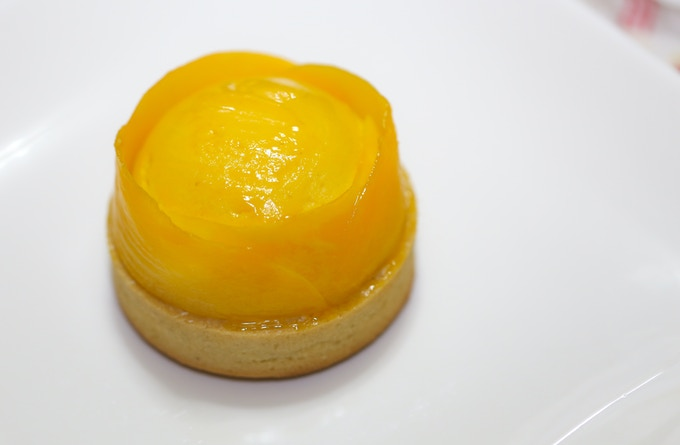 Mango Coconut Tart: Sweet almond crust with coconut and mango mousse covered with mango glaze and lined with fresh mango slices
