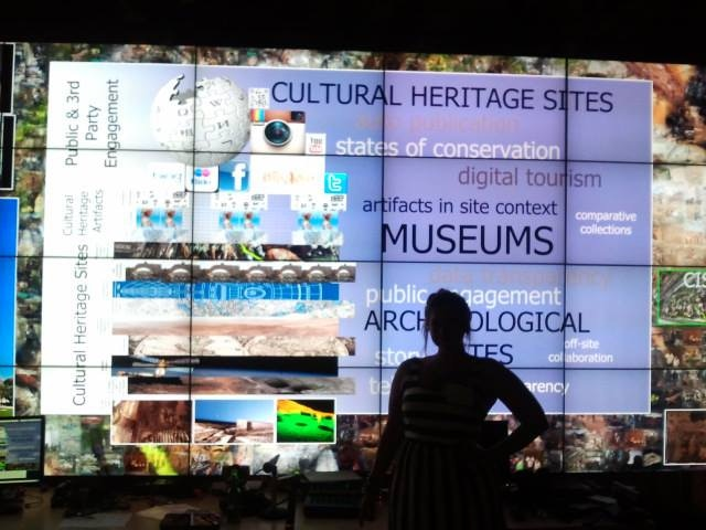 Ashley in front of one of the Qi visualization walls displaying Vid and Ashley's research on layered digital realities for cultural heritage data collection and analysis.