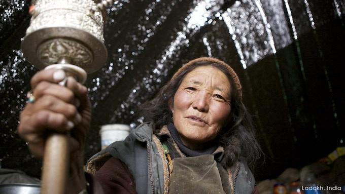 Ladakhi woman with her prayer wheel in an animal skin tent. Ladakh, India.