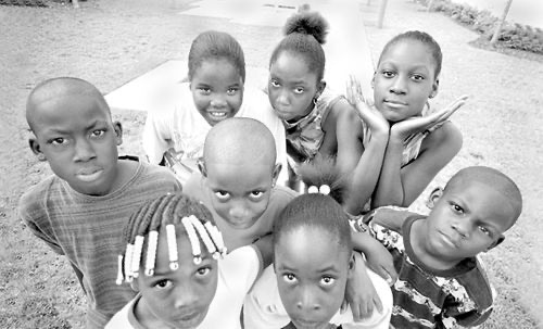 Ten-year-old Otius, hands framing her face, with homeless friends who share the secret stories.
