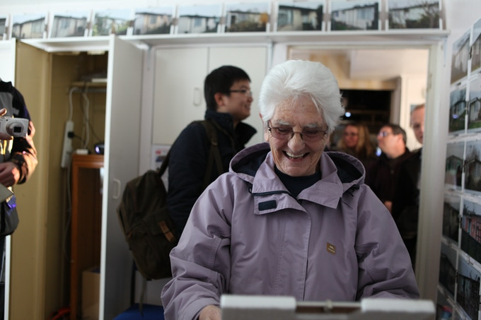 Joan, prefab resident, picking up a photo of her loved prefab, March 2014