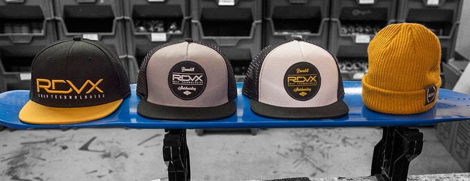 Caps to Choose From (Left to Right): RDVX Gold Snapback, Black on Grey Trucker, Gold on White Trucker and Logo Beanie.
