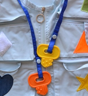 Around the neck are strings that run down the center of the vest with teethers on both tips.  Your baby will enjoy pulling down on one teether and watching the other teether go up.